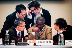 """Bubu Jallow (Mitte), einer der Insider, über die """"Das Paris-Protokoll"""" berichtet. Er ist Mitglied der Delegation Gambias, hier berät er sich in einer Verhandlungspause mit Vertretern anderer Länder. Foto: Das Paris-Protokoll"""