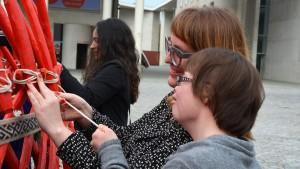 Die Leiterin des Forschungsprojektes Katja de Bragança, die Übersetzerin in klare Sprache, Anne Leichtfuß und Beiratsmitglied Julia Bertmann (v.l.) binden zusammen die letzten Stangen der Jurte fest. Foto: Vera Lisakowski