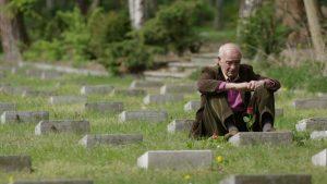Filmstill: Carmine Mancini, Sohn eines Opfers, besucht den italienischen Militärfriedhof in Berlin-Zehlendorf.