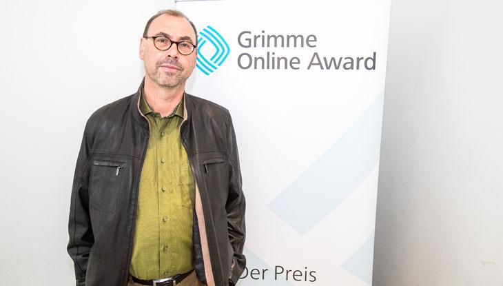 """Rüdiger Braun, Autor von """"Das Geheimnis des Groove"""", vor einem Rollup des Grimme Online Award bei der Bekanntgabe der Nominierungen 2018. Foto: Rainer Keuenhof / Grimme-Institut"""