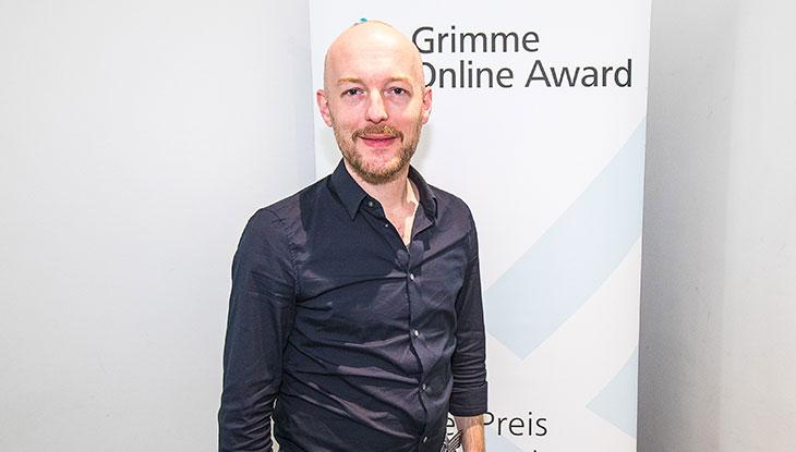 """Boris Rosenkranz, Mitbegründer von """"Übermedien"""", vor einem Rollup des Grimme Online Award; Foto: Rainer Keuenhof/Grimme-Institut"""