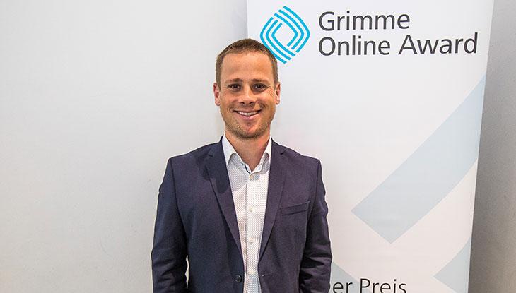 Chefredakteur Yannick Dillinger bei der Bekanntgabe der Nominierung in Köln, vor einem Rollup des Grimme Online Award; Foto: Rainer Keuenhof/Grimme-Institut