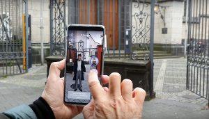 """Hände halten ein Smartphone mit einem animierten Beethoven, Standbild aus dem Video zur App """"BTHVN2020""""; Quelle: """"Bürger für Beethoven"""" auf YouTube"""