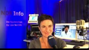 Frau im Radiostudio. Hinter ihr Bildschirme, Mikrofon und ein Aufsteller von NDRinfo.