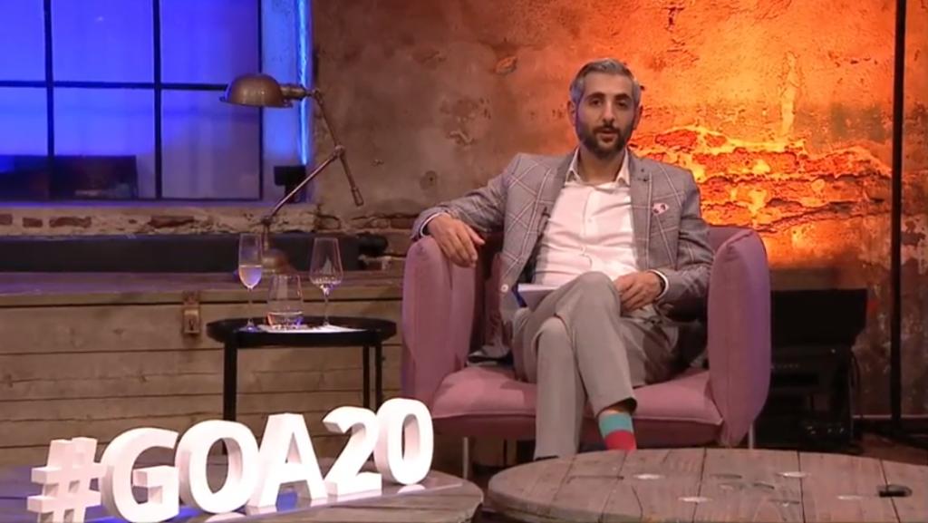 Michel Abdollahi sitzt auf einem rosanen Sessel, vor ihm ein runder Holztisch mit dem #GOA20 Schriftzug, neben ihm ein Beistelltisch mit Wasser-; Wein- und Sektglas